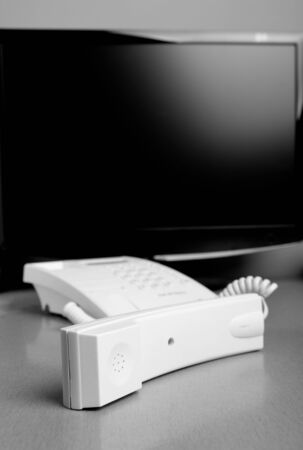White phone with a computer monitor in the background photo