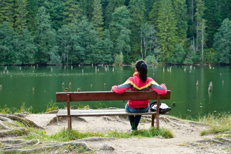Woman sitting on a bench near the lake Imagens