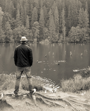 Man standing looking away onto the lake (sepia effect) photo