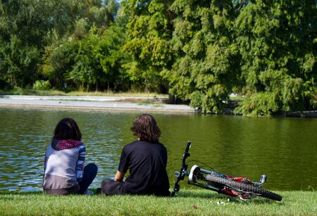 Teens sitting on the grass in the park photo