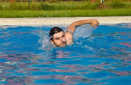 Man swimming in the pool with water splashing photo