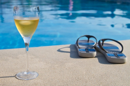 Glass of white wine next to the pool photo
