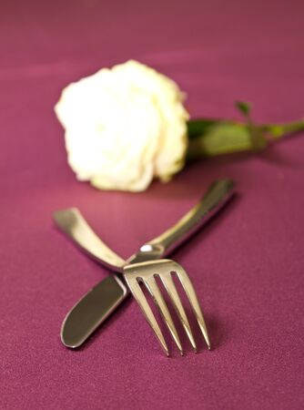 White rose behind silverware setting photo