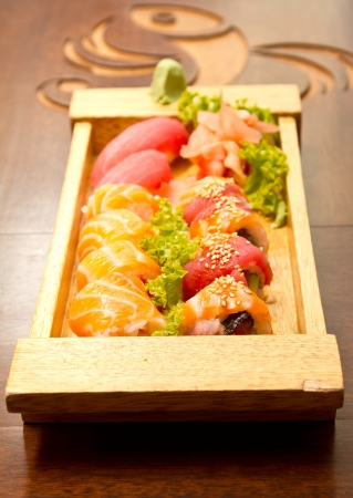 Different kinds of sushi on a wood plate photo