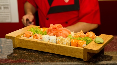 Different kinds of sushi on a wooden plate (shallow DOF) Stock Photo - 15861676