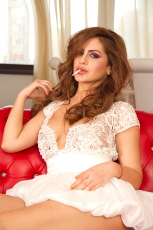 Beautiful girl smoking on the couch