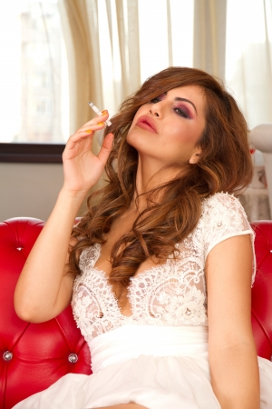 Beautiful girl sitting on the counch and smoking photo