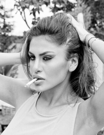 Beautiful woman smoking and playing with her hair photo