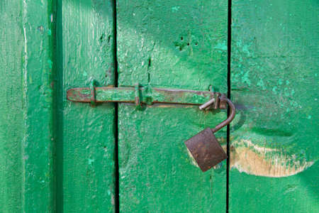 Grungy door with an old unlocked lock photo
