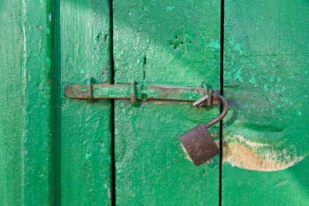 unlocked: Grungy door with an old unlocked lock