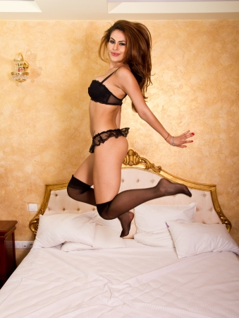 Beautiful woman jumping in bed photo