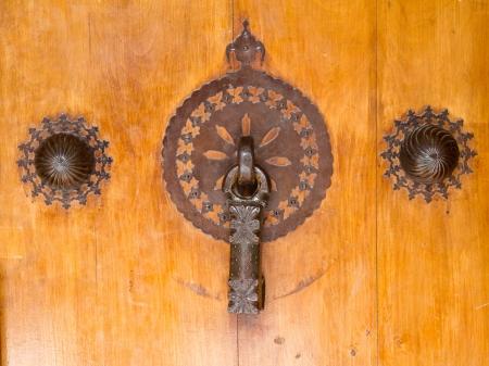 Ornamental door knob on a wooden door photo