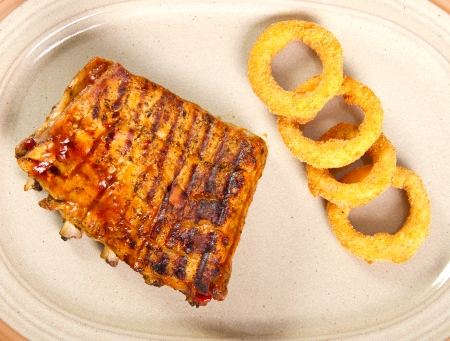 Grilled pork ribs with onion rings photo