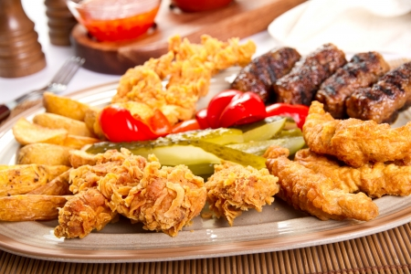 Mixed grilled and fried  meat platter and pickles photo