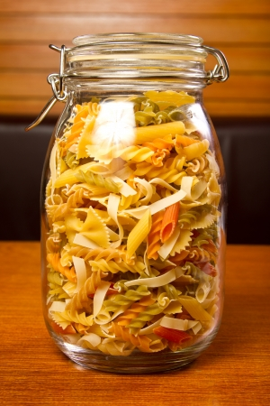 Different types of raw pasta in a glass jar photo