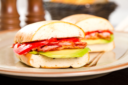 Sandwich with fried bacon avocado and tomatoes photo