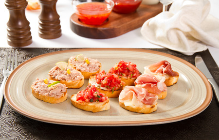 Bruschette with tomatoes, tuna and prosciutto photo