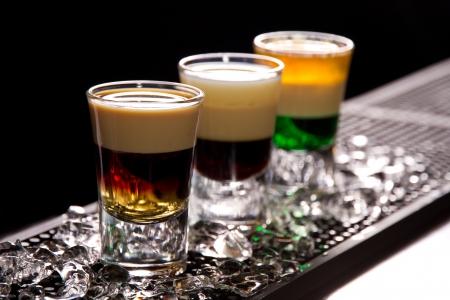 Three layered shots on a bar counter top photo