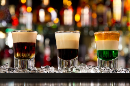 Three layered shots on a bar counter top