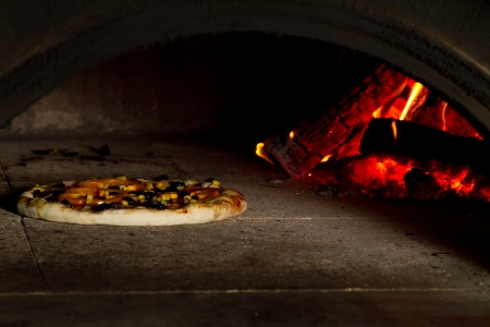 Pizza baking in a wooden fire oven photo