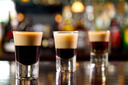 amaretto: Three layered shots on a bar counter top