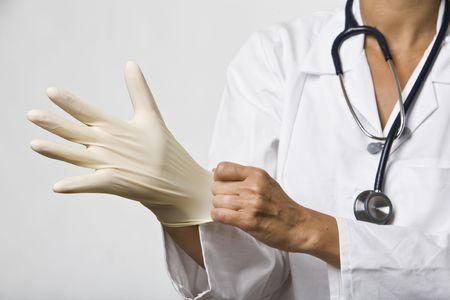 plastic glove: Doctor pulls on a latex glove. Stock Photo