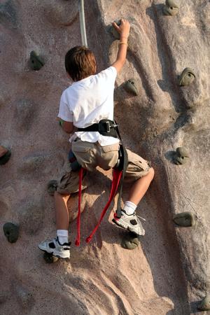 climbing  wall: Kid climbing wall Stock Photo