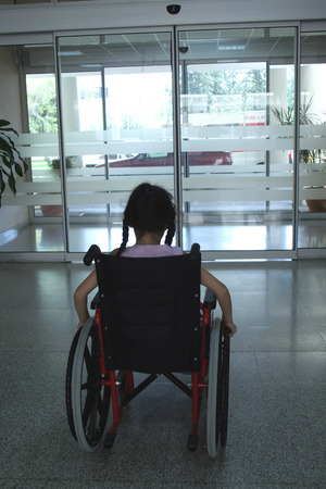 Young girl on wheelchair leaving hospital photo