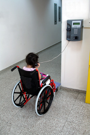 Young girl on wheelchair making a phone call photo