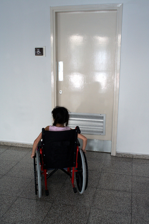 Young girl on wheelchair entering wc for disabled people photo