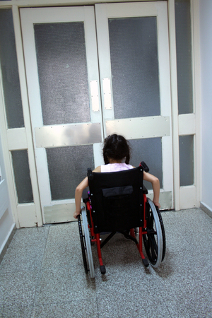 Young girl on wheelchair in front of closed doors photo