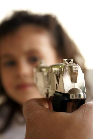 A gun aiming at a childs face
