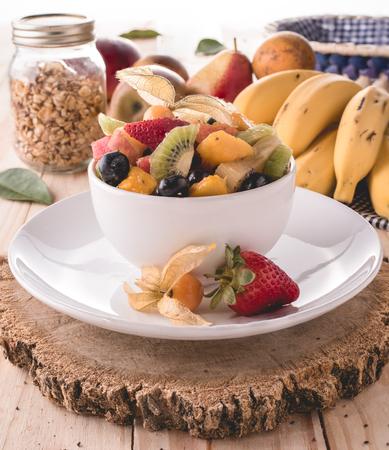 Tropical fruit salad served in white pot (Grape, banana, star fruit, strawberry, melon, pear, kiwi, apple, pineapple)