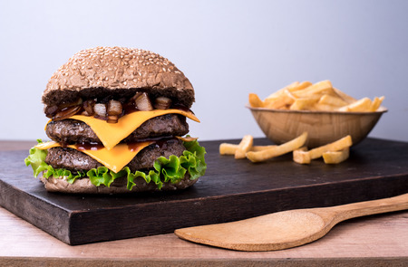beef burger with salad, caramelized onion and tomato on top of a wooden board and white background