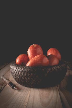 Injection of poisonous toxin into an organic tomato Фото со стока