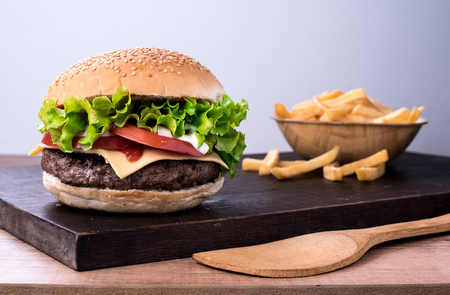beef burger with salad and tomato on top of a wooden board and white background