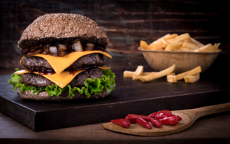 Traditional spicy beef burger with salad, caramelized onion and tomato on top of a wooden board and rustic background