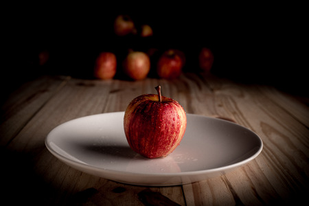 An organic apple on a wooden table and black background