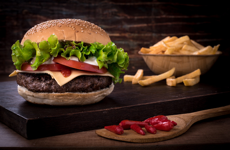 Traditional spicy beef burger with salad and tomato on top of a wooden board and white background Фото со стока