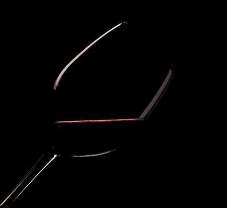 Glass of red wine on a black background Фото со стока