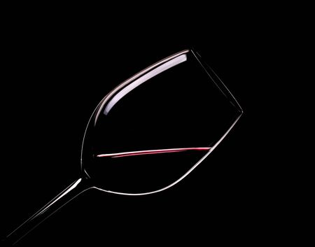 Elegant glass of red wine on a black background.