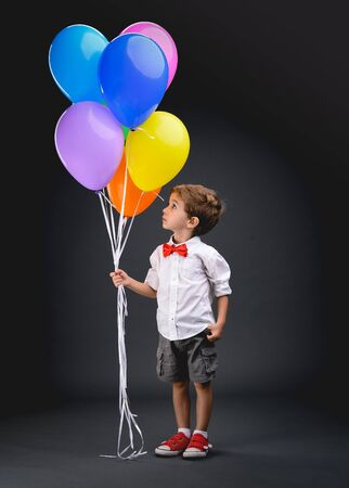 Little boy playing with colorful balloons (bladders)