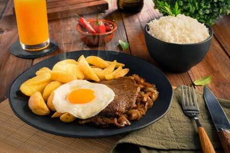Lomo a lo Pobre - Traditional Chilean Food - Meat, rice, chips and caramelized onion