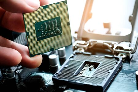 Hand of computer engineering brings computer cpu processor memory change components into socket processor for maintenance.Technology and development concept Stock Photo