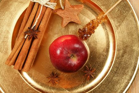 Red apple, cinnamon and anise stars on golden plate. Christmas fragrant composition photo