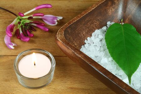 Spa resort therapy composition, candle, honeysuckle flower, leave and salt crystals photo