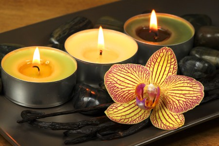 scented candle: Three burning candles and orchid flower with vanilla pods. Aromatic spa treatment Stock Photo