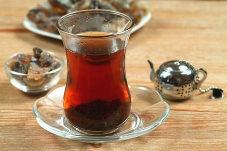 Tea prepared in turkish way, cane sugar and small steel teapot. Five oclock photo