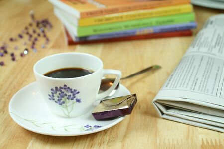 fresh news: A cup of morning coffee surrounded with newspaper and colorful books. Optimistic day.