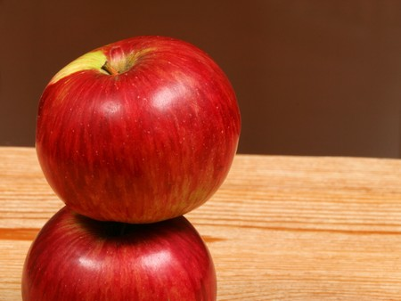 Two red juicy apples in vertical composition on wooden table photo